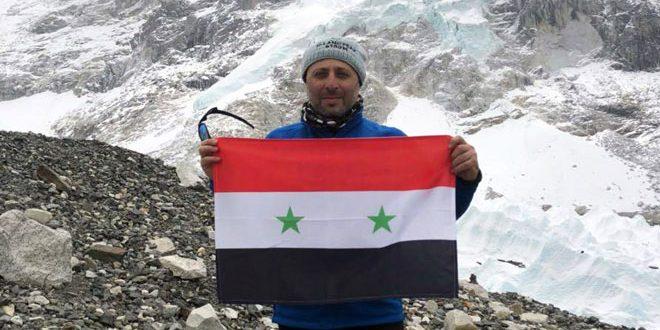 Un syrien hisse le drapeau national sur les montagnes de l'Himalaya